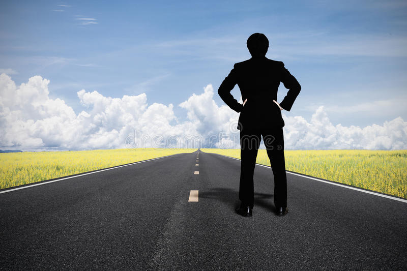 Businessman standing on the road. Concept of the road to success with a businessman standing on the road royalty free stock image