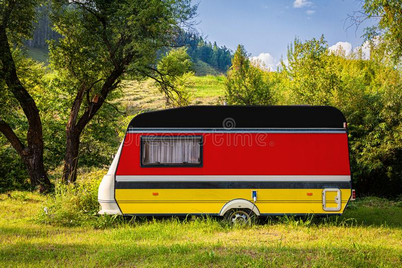 The concept of road transport, trade, export and import between countries. A car trailer, a motor home, painted in the national flag of Germany stands parked in royalty free stock image
