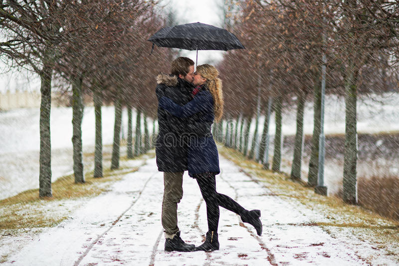 Concept of romance. Young couple kissing in snowdrift, concept of romance stock image