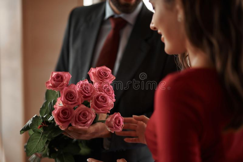 Young man presenting smiling woman pink roses. Concept of romantic date atmosphere. Close up portrait of gentleman presenting pink roses to smiling beautiful stock photos