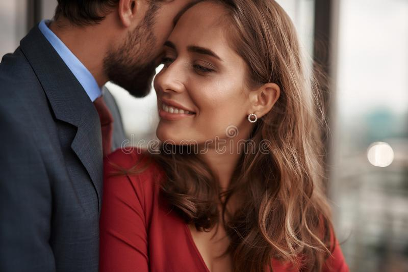 Happy young male and female having romantic meeting. Concept of romantic date. Close up portrait of happy beloved lady clinging with love to her male lover while stock photography