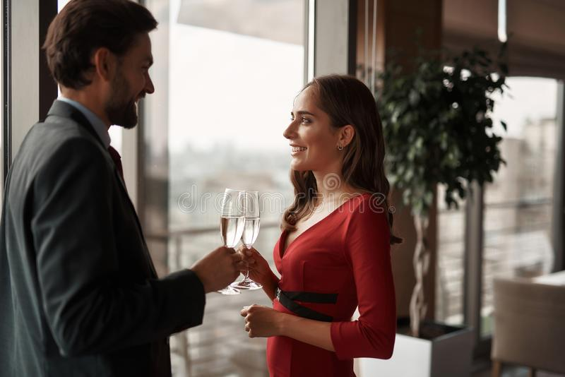 Young man and woman have romantic meeting. Concept of romantic date. Waist up portrait of happy beloved couple with champagne glasses celebrating in restaurant royalty free stock photo