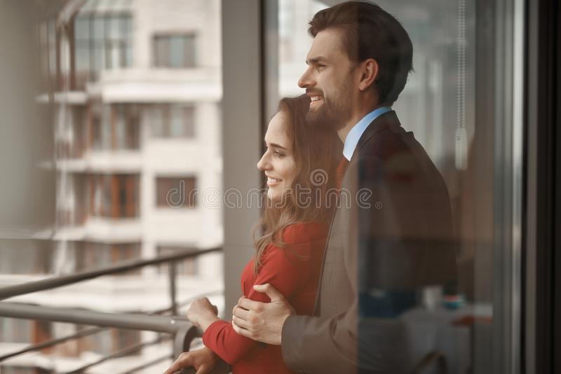 Young man and woman having romantic meeting outdoor. Concept of romantic date. Waist up portrait of happy beloved couple standing in arms of each other on stock image