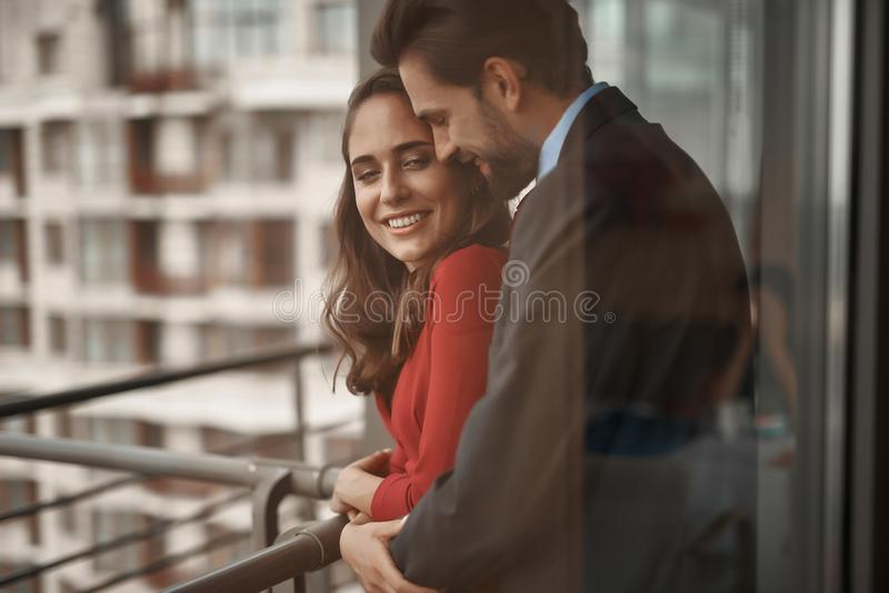 Smiling man and woman having romantic meeting. Concept of romantic date. Waist up portrait of happy beloved couple standing in arms of each other on balcony and royalty free stock photos