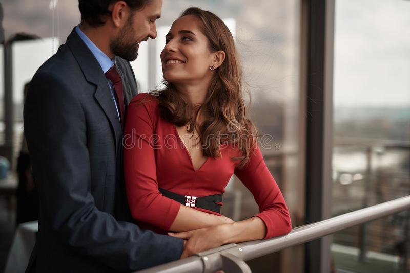 Happy man and woman having romantic meeting. Concept of romantic date. Waist up portrait of happy beloved lady looking with love to her male lover while standing stock photo