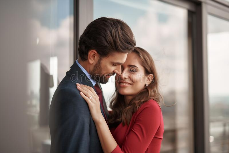 Smiling young male and female having romantic meeting. Concept of romantic engagement. Waist up portrait of happy beloved lady with golden ring on finger stock image