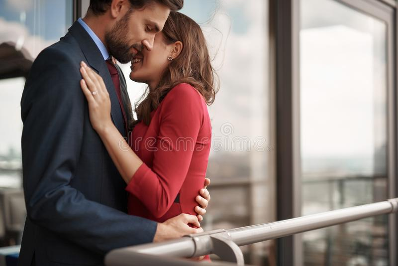 Happy young man and woman staying outdoor. Concept of romantic love. Waist up portrait of happy beloved couple embracing together with tender while standing on royalty free stock images