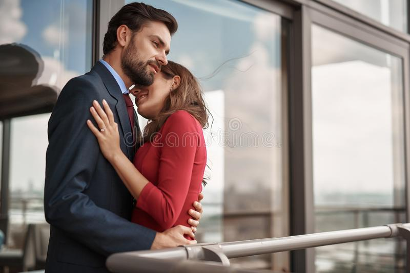 Adult man and woman having romantic meeting out door. Concept of romantic love. Waist up portrait of happy beloved lady clinging to her male lover while standing stock photography