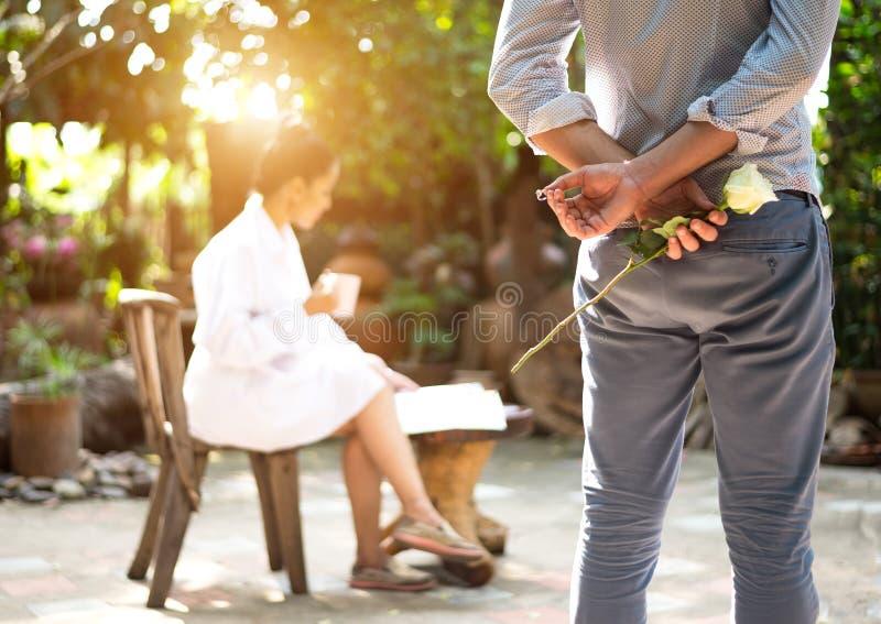 Concept romantique avec l'homme jugeant la rose et l'anneau de blanc faisant le mariage photo stock