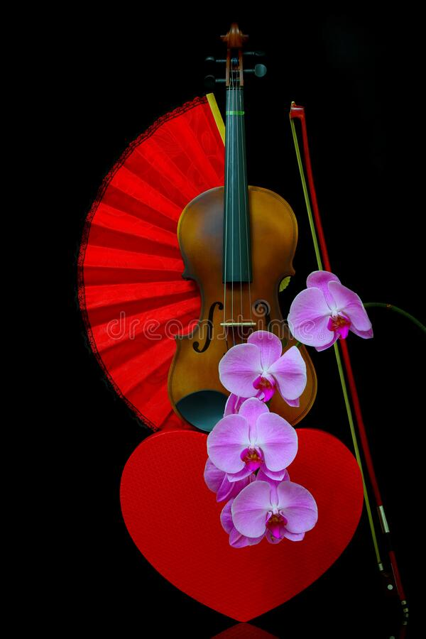 Concept romantique avec violon, boîte cadeau en forme de coeur, ventilateur pliant rouge et orchidées roses photo libre de droits