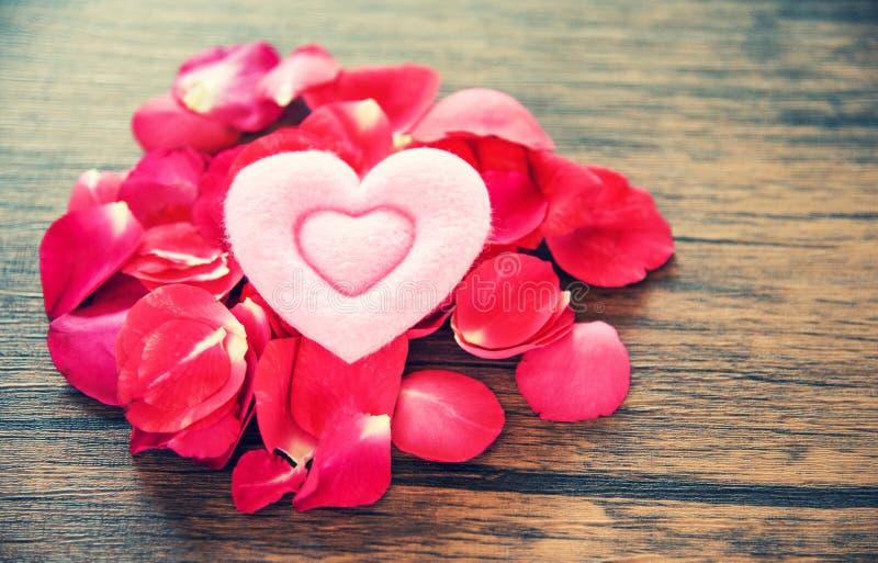 Concept romantique de coeur d'amour de jour de valentines/pile des pétales de roses avec le coeur rose décoré image stock
