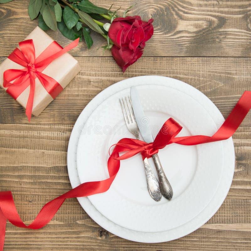 Concept romantique de dîner Arrangement de fête de table pour le jour de valentines sur le fond en bois Rose de rouge et cadeau r photographie stock