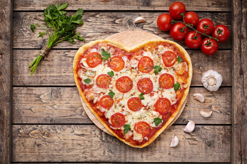 Concept romantique de nourriture d'amour de margherita en forme de coeur de pizza avec du mozzarella, les tomates, le persil, et  image libre de droits