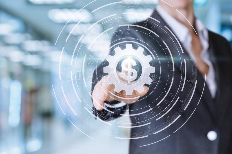 The concept is the running banking system. A businesswoman is touching a cogwheel button with a currency unit inside on the touch screen at the office background royalty free stock images