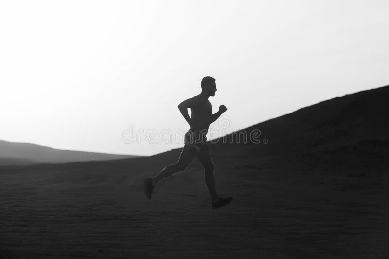 Concept of running. Man runner running in dune at sunset stock photography