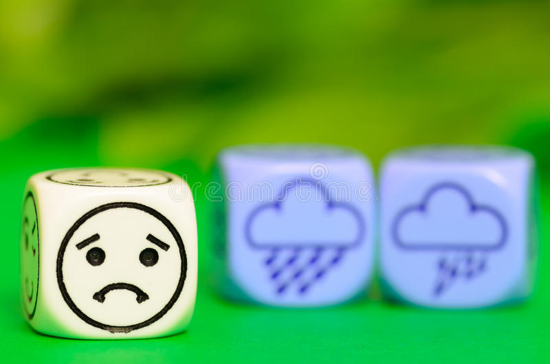 Concept of sad storm weather - emoticon and weather dice on green backround. Stock photo royalty free stock images
