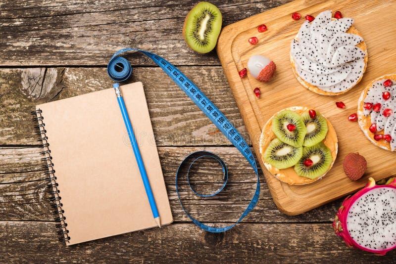 Concept sain de nutrition de régime de mode de vie Casse-croûte sain des gâteaux de riz avec des fruits Carnet, crayon, bande de  photos libres de droits