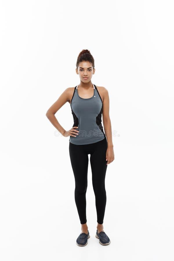Concept sain et de forme physique - le portrait de la fille d'Afro-américain posant avec la forme physique vêtx au-dessus du fond photo libre de droits