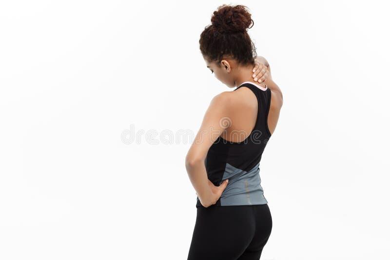 Concept sain et de forme physique - le portrait de la fille d'Afro-américain subit un préjudice de muscle se tenant tenant son co photo libre de droits
