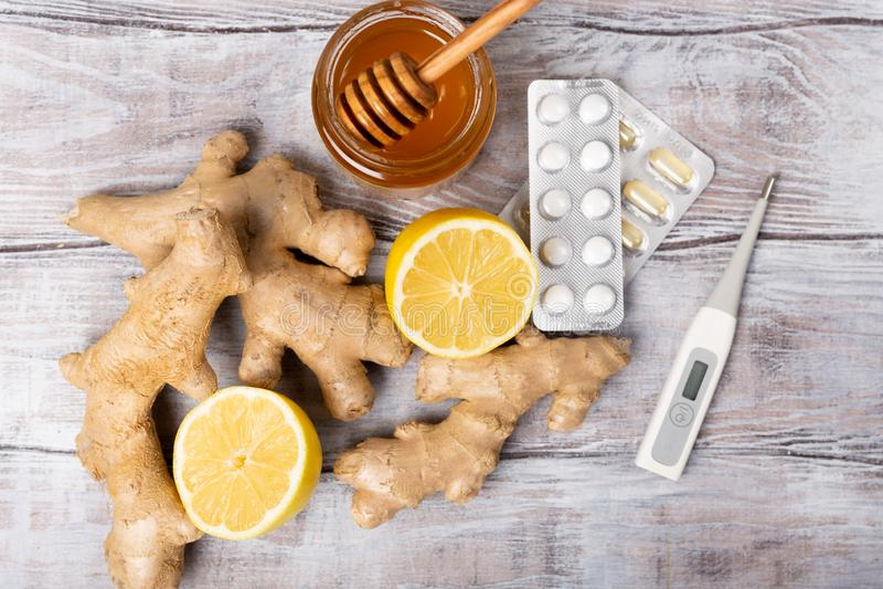 Concept sain Thé, citron, thermomètre, gingembre, miel et comprimés sur un fond blanc Configuration plate Traitement du froid photo stock