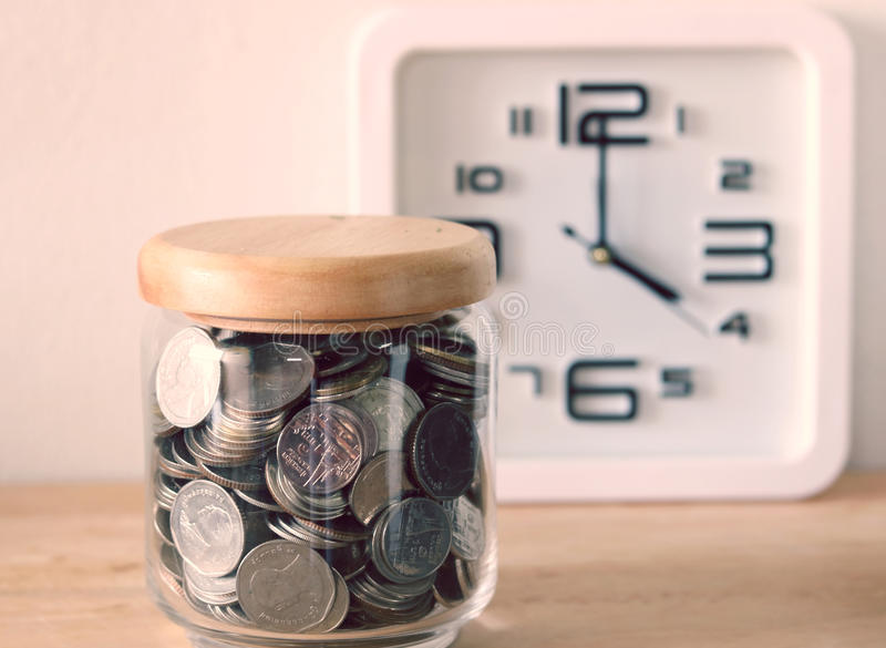 The concept of saving money. A clock is behind the scenes with filter effect retro vintage style stock photo