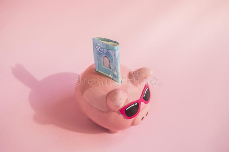 Concept of saving money on your trip or vacation pig piggy Bank with sunglasses on the bill of euros on a pink background, place royalty free stock image