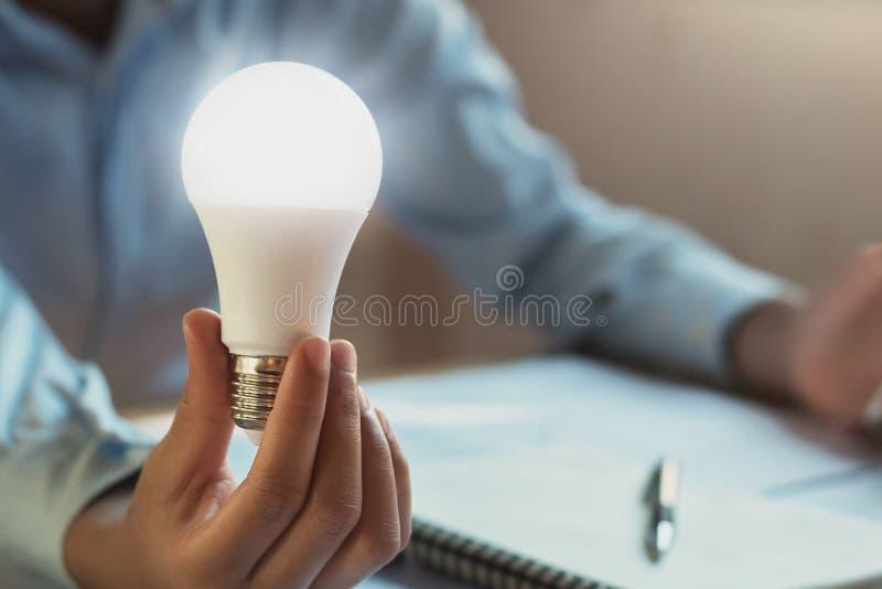 Concept saving power energy. Hand show led bulb royalty free stock photo