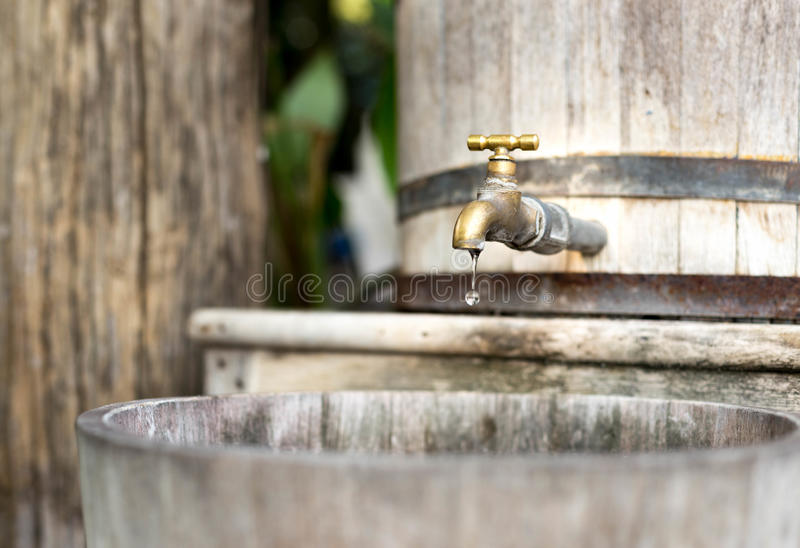 Concept saving water wooden water tank with golden tap and in s. Concept saving wooden water tank with golden tap and drop of water in soft background stock images