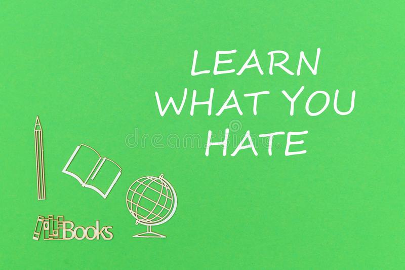 Text learn what you hate, school supplies wooden miniatures on green background. Concept school for kids, text learn what you hate, school supplies wooden royalty free stock photos