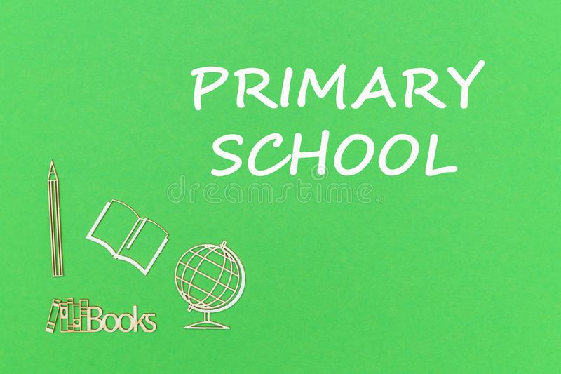 Text primary school, school supplies wooden miniatures on green background royalty free stock image
