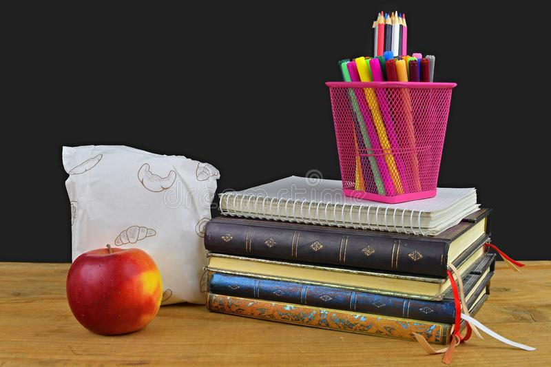 Concept of school lunch break with apple and school supplies on wooden desk, selective focus. Books, markers and color stock photo