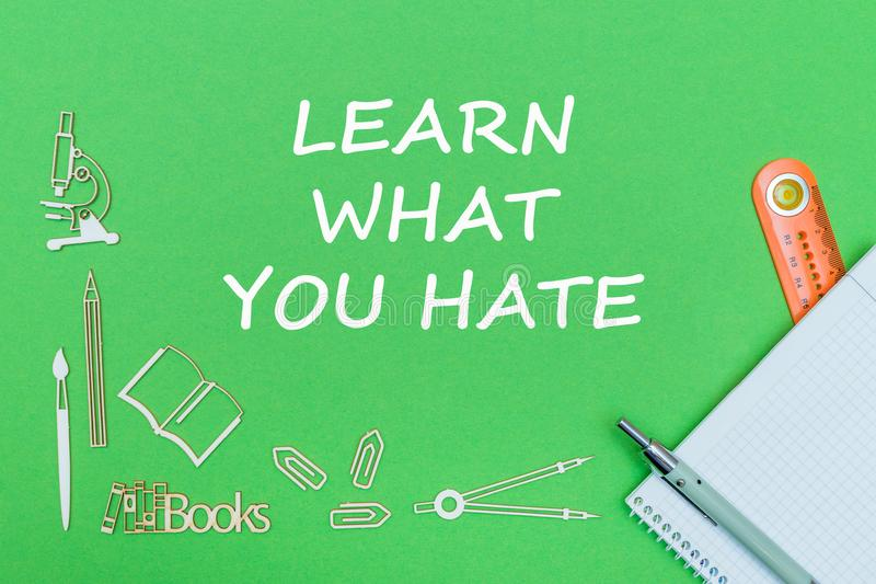 Text learn what you hate, school supplies wooden miniatures, notebook with ruler, pen on green backboard. Concept school, text learn what you hate, school stock photography