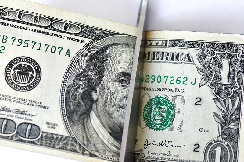 Concept scissors cut the hundred dollar and one dollar bill on white background stock photos