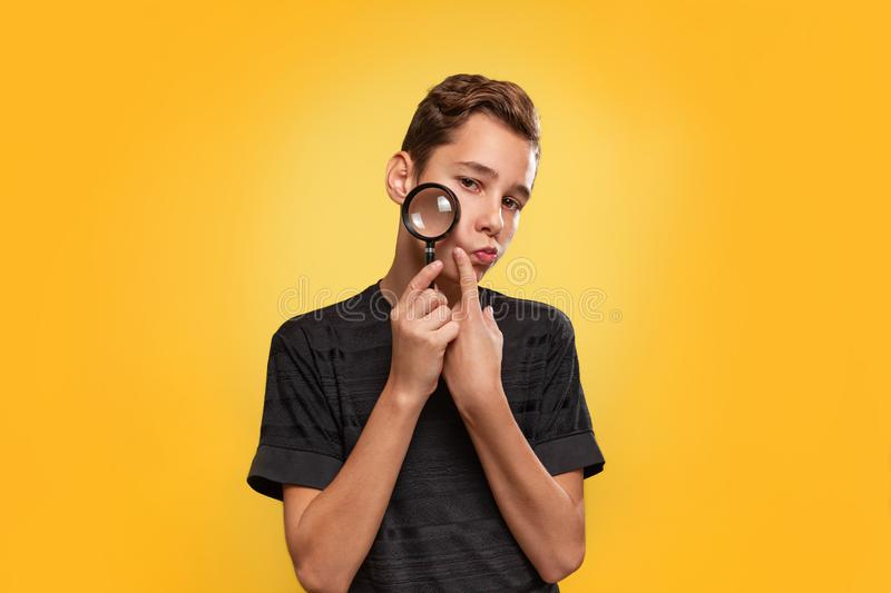 The concept of search. A teenager in a black t-shirt, presses a paw to his cheek. Yellow background. Copy space stock photography