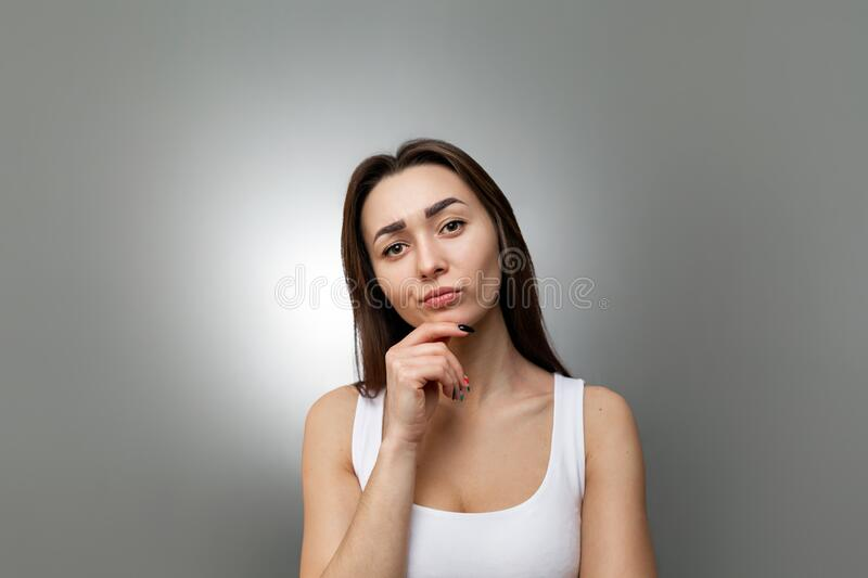 The concept of searching for ideas and information. Portrait of a pensive young Caucasian woman with her hand on her chin. Grey stock image