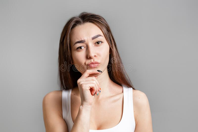 The concept of searching for ideas and information. Portrait of a pensive young Caucasian woman with her hand resting on her chin stock photos
