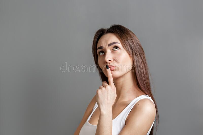 The concept of searching for ideas and information. Portrait of a pensive young Caucasian woman looking at the top and putting her royalty free stock photos