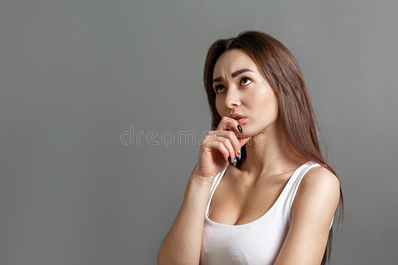 The concept of searching for ideas and information. Portrait of a pensive young Caucasian woman putting her finger to her mouth. stock photo
