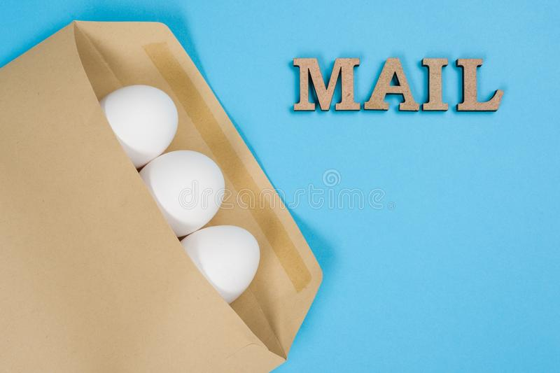 The concept of secure courier service, reliable postal company. Abstract image of eggs in an envelope and the word mail, post. stock images