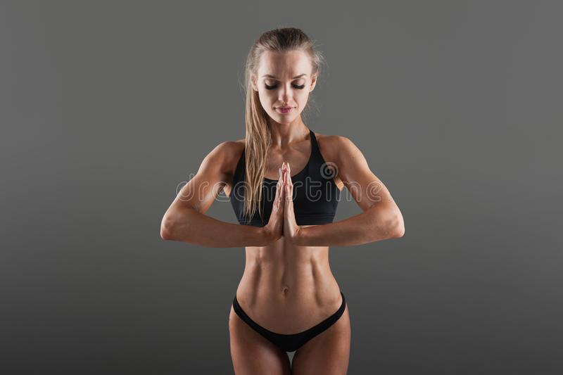 The concept of self-control in sports. Meditation before hard training. A beautiful girl in black sports clothes stock photo