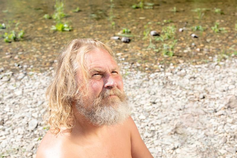The concept of self-knowledge, communication with God, the search for yourself. elderly man with pensive view on shore. The concept of self-knowledge stock photos
