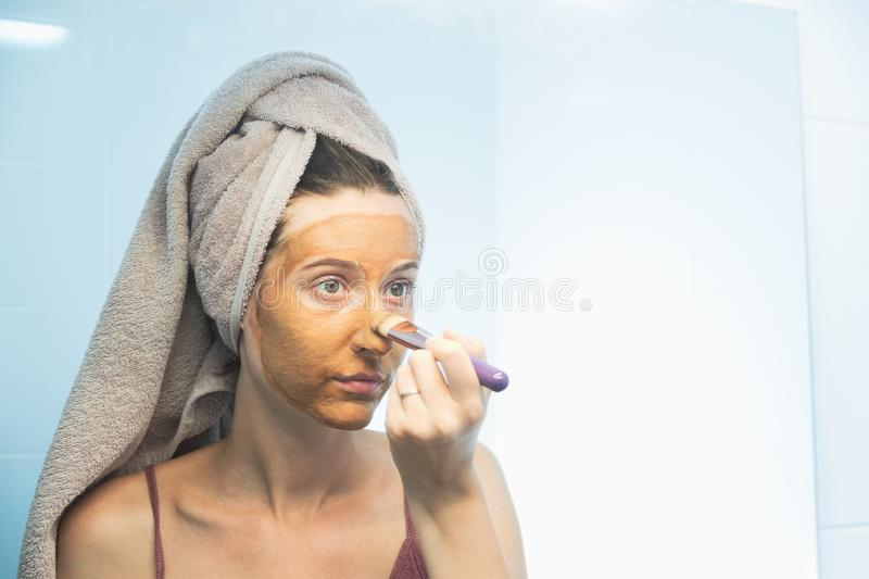 A young woman puts a clay mask on her face with a brush. stock photos