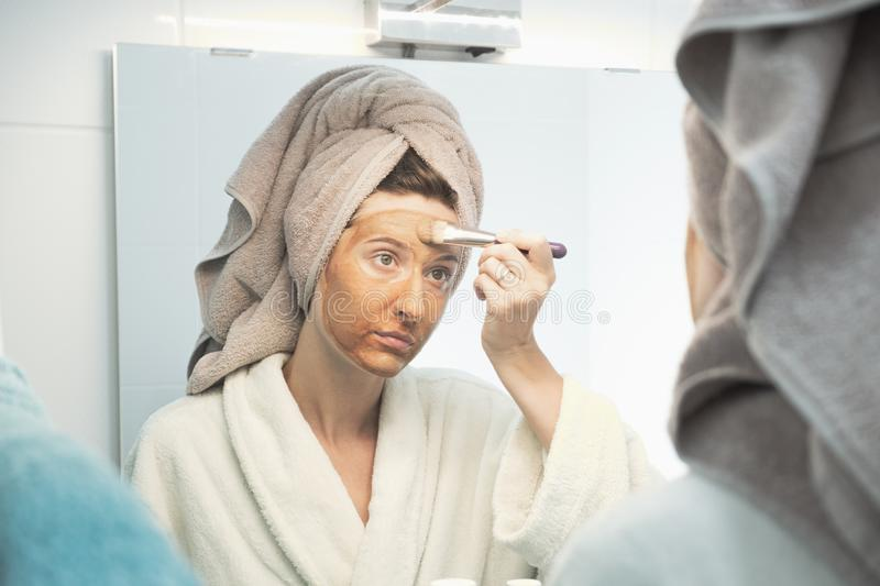Young woman puts clay mask on her face after shower looking in mirror in bathroom. stock images