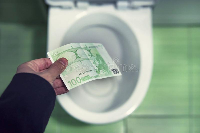 Concept of senseless waste of money, loss, useless waste, large water costs, money and toilet showing financial crisis royalty free stock photography