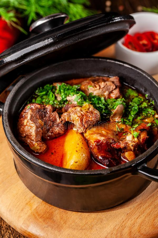The concept of Serbian cuisine. Juicy baked beef in its own juice with potatoes, vegetables and greens. Serve in an iron fire royalty free stock images