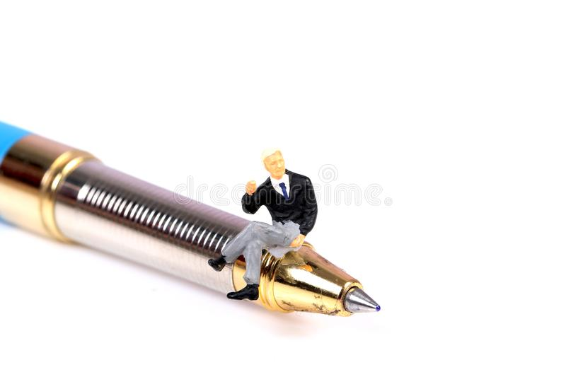 Happy writer. Concept shot showing miniature male sitting on the tip of ball pen royalty free stock image