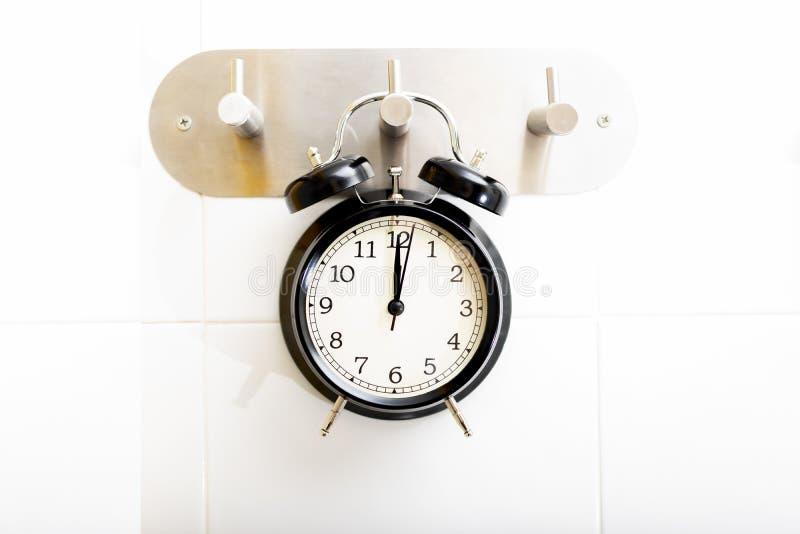 Concept showering time. Black alarm clock. Hanging on a shower hanger stock photo