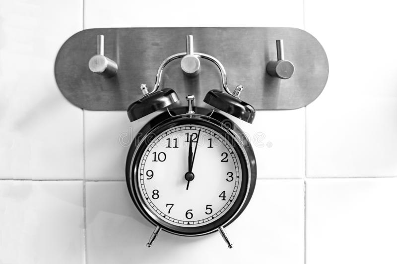Concept showering time. Black alarm clock. Hanging on a shower hanger royalty free stock photo