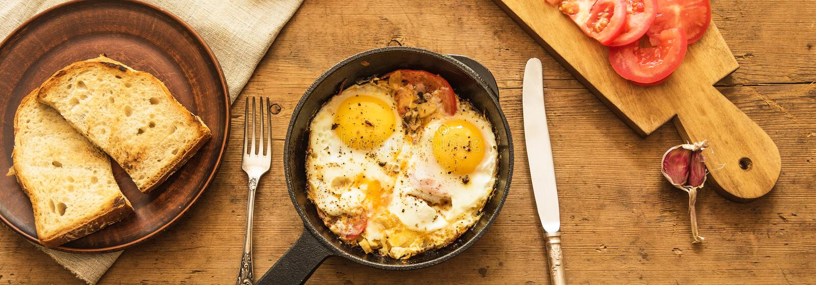 Fried eggs in a frying pan, bread and tomatoes with garlic on a rustic wooden background, top view. The concept of simple healthy eating, panoramic banner with a stock photos
