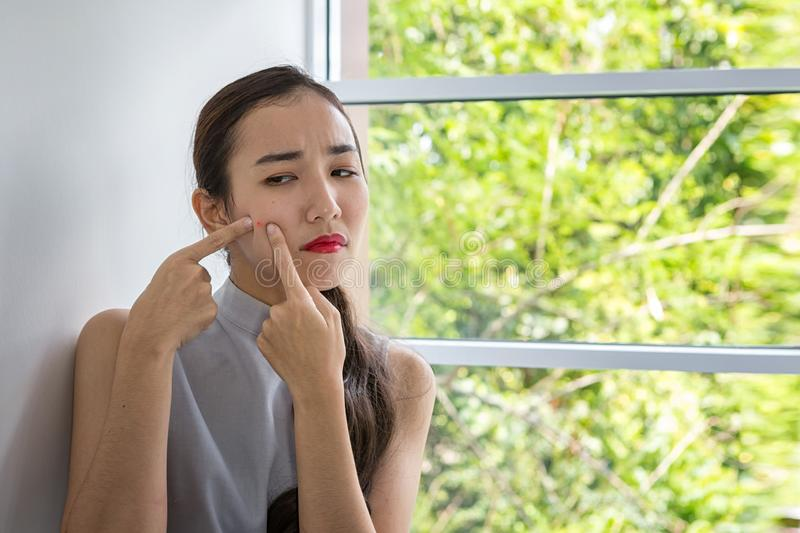 Concept for skin care and face problem. The girl is dismayed with acne on the face. Asian woman unhappy touching her skin royalty free stock photos